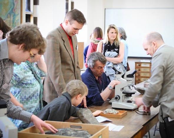 Alumni and their families taking part in an Alumni Day activity, using microscopes