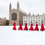 Choirboys from King's College Choir walking in the snow in front of the chapel