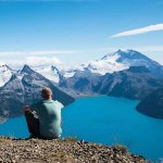 Man sitting on mountain surveying view, Unbound 10 cover image
