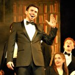 Musical theatre production with actors in formalwear