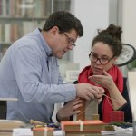two people working on conservation of a book