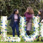 'Lucy' spelt out in flowers with members of the Committee