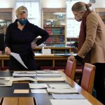 Dr Katrina Dean, Keeper of Archives and Modern Manuscripts, studying some of the paper archive with Dr Jessica Gardner, Universi