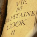 Close up of old book spines on the Life of Captain Cook with French titles