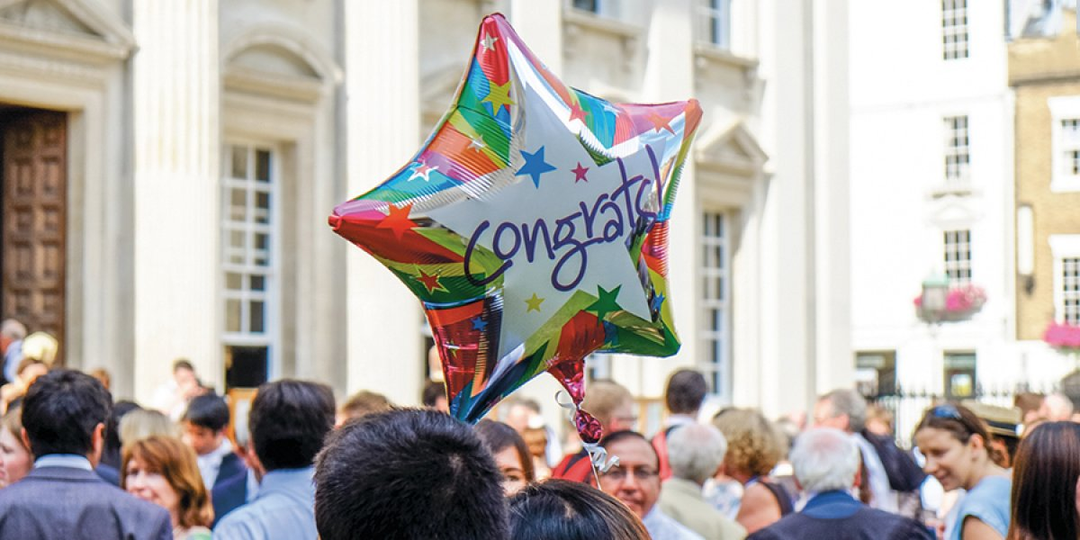 Congrats balloon amongst crowd on Senate House Lawn at graduation