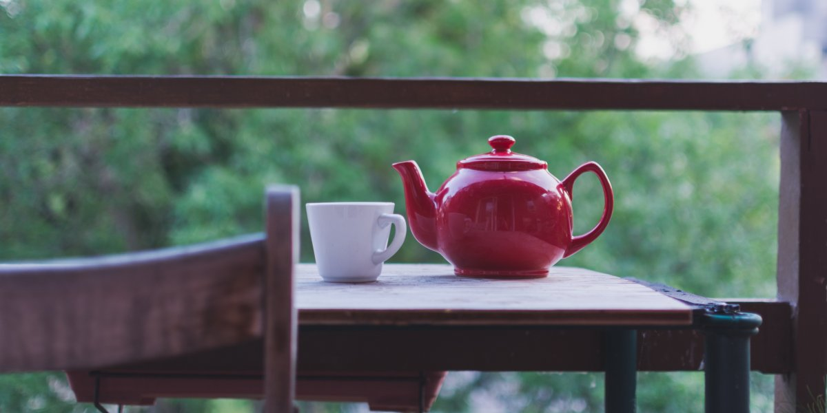 Red teapot on a table with green scenery in the background