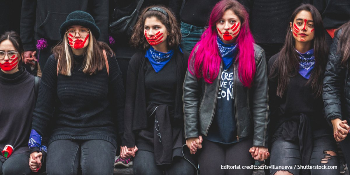 Line of women with a red hand print over their mouths