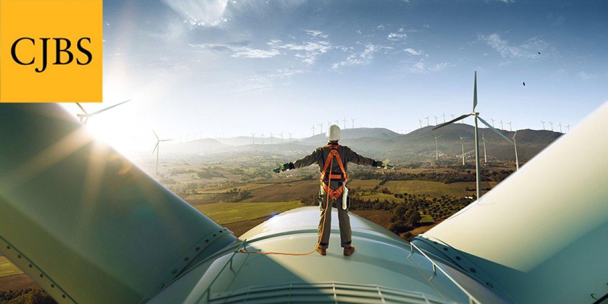 Man standing on top of a wind turbine with CJBS logo in top left corner